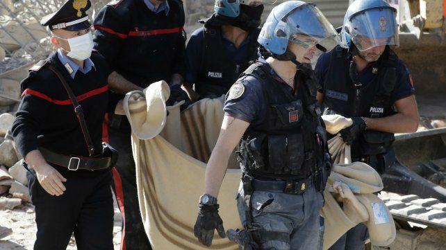Efectivos policiales y socorristas trasladan el cadáver de una de las víctimas enAmatrice