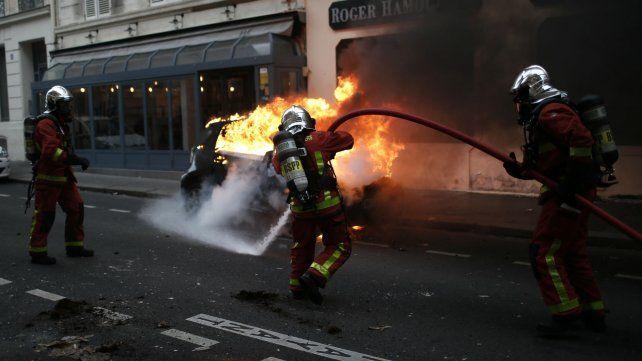 Bomberos atacan el incendio de un auto en pleno centro parisino.