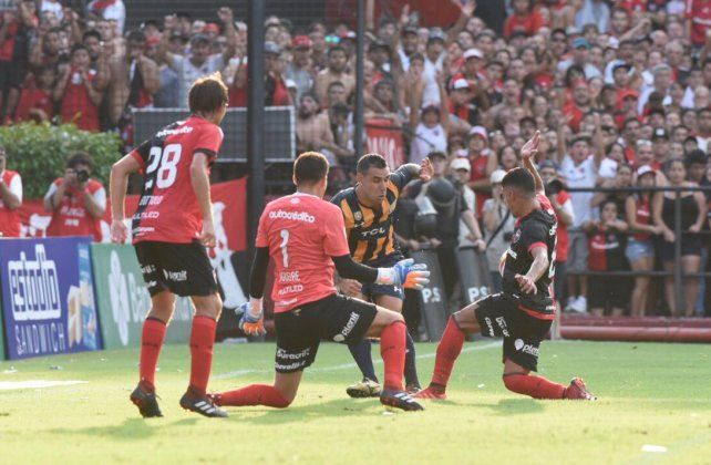 El Chaco Herrera maniobra ante Aguerre y Rivero. El juez había anulado la jugada por supuesta falta del delantero.