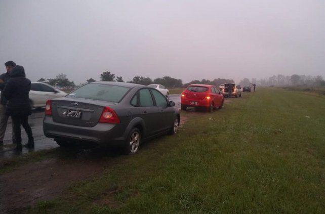 La fila de autos con las llantas rotas a la vera de la autopista.