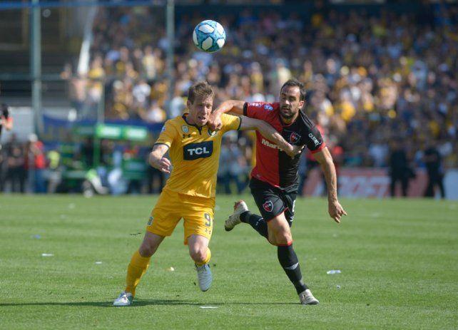 Gentiletti trata de frenar la potente entrada de Claudio Riaño.