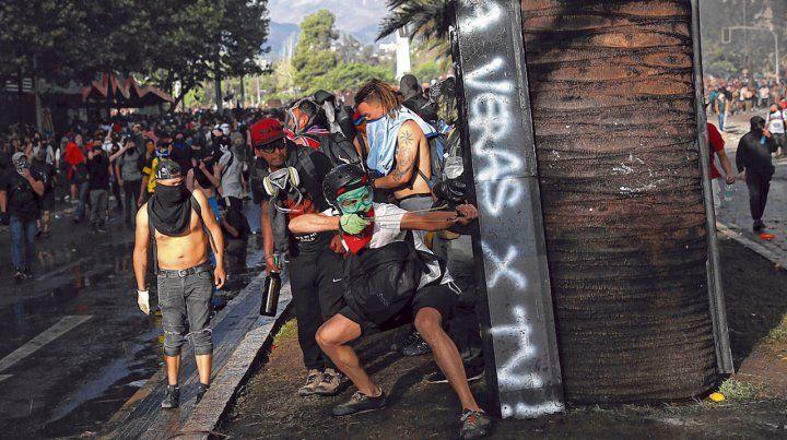 caos continuado. Un activista apunta con un tiro de gomera a la policía carabinera en un sector del centro de Santiago