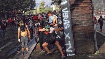 caos continuado. Un activista apunta con un tiro de gomera a la policía carabinera en un sector del centro de Santiago, la capital.