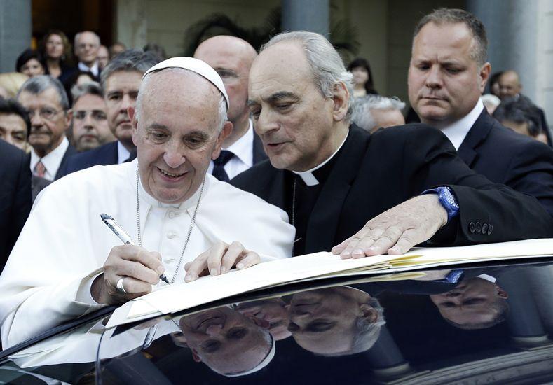 El Papa firmó el documento sobre el techo de un auto. (Foto: AP)
