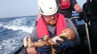 La foto del rescatista con un bebé migrante: Lo protegí como si aún estuviera vivo