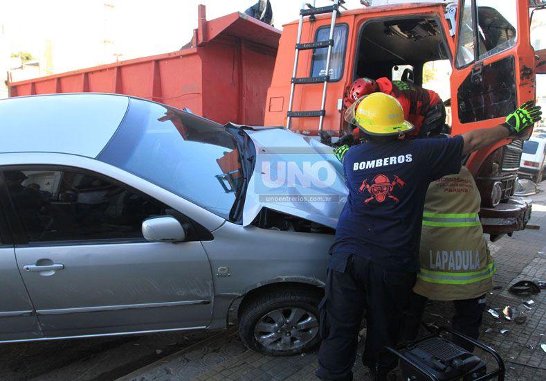 Los bomberos trabajando para separar el vehículo del camión. Foto UNO Diego Arias.