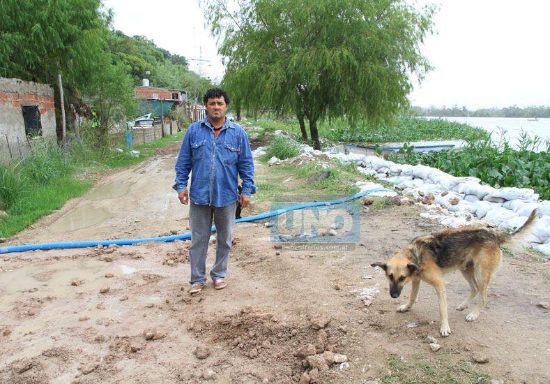 El Tingue Villalba en el barrial de Puerto Sánchez junto a uno de los perros que se alimentan de la pesca. Foto UNO Juan Ignacio Pereira.