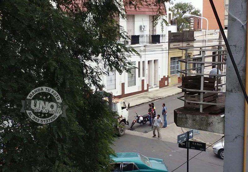 El conductor del camión y el motociclista cruzando datos en la esquina del accidente.