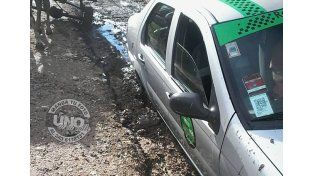 El remisero ayer perdió su día de trabajo porque el auto quedó enterrado en el barro.