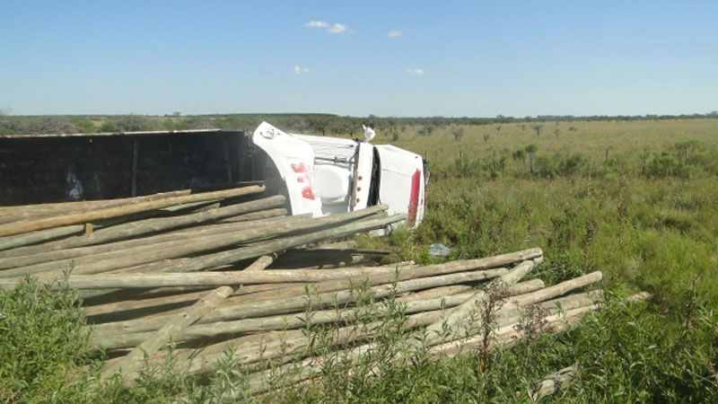 Un camión con postes de madera chocó y volcó su carga