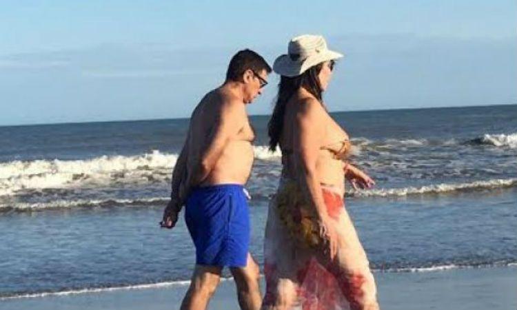 Moria Casán camina junto a un amigo por la orilla del mar.