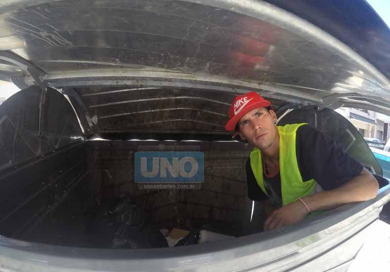 Mientras espera por un trabajo busca entre las sobras del contenedor