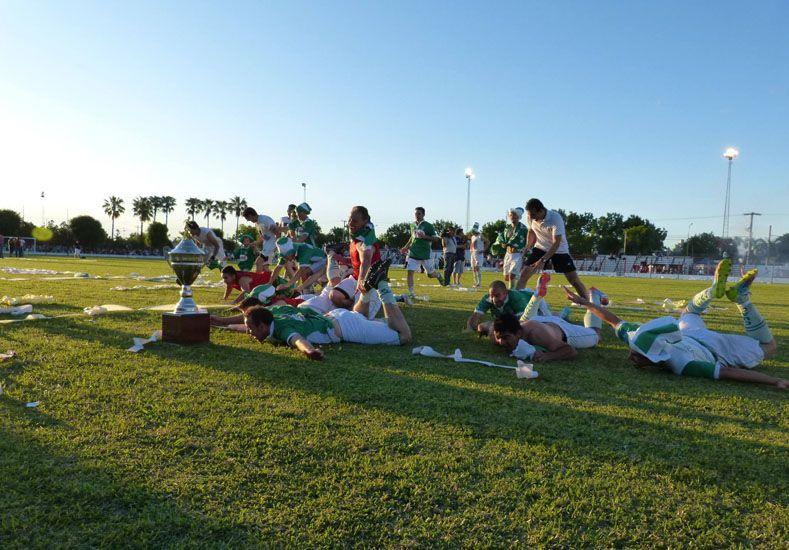 Los jugadores del monarca festejan junto a la copa que lograron ayer en María Grande.