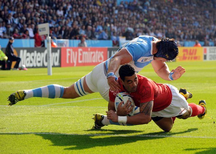 Nicolás Sánchez y intenta detener un try de Tonga.
