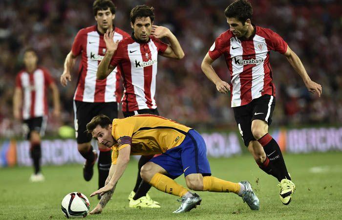Messi se tropieza y cae anta la presencia de los vascos Merino y Susaeta. (Foto: AP)