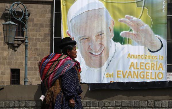 Una indígena pasa delante de una gigantografía del Papa anunciando su llegada a La Paz. (Foto: AP)
