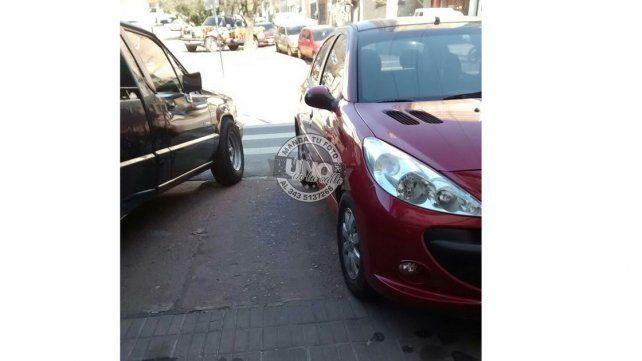 Dos autos bloquean el paso hacia la senda peatonal.