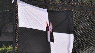 Bandera albinegra con la remera de Marisa detrás del arco.