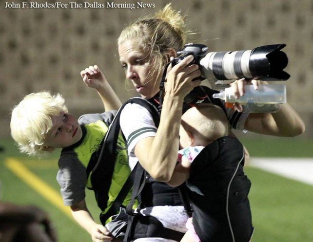 La mamá sacando fotos ene le partido de fútbol americano.
