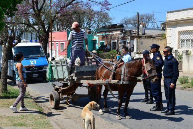 Un trabajador municipal habla con el dueño del carro mientras los policías controlan la situación. Foto Municipalidad de Paraná.