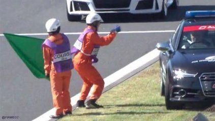 Un comisario de pista bailando en un autódromo