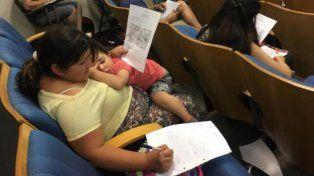 La foto que emociona: una madre rindió un examen con su hija en brazos
