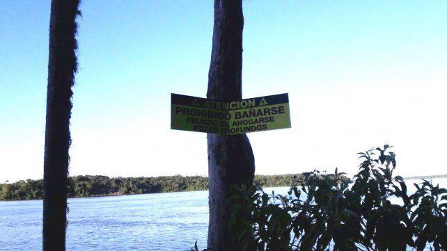 El cartel que advierte sobre el peligro de nadar en la zona.