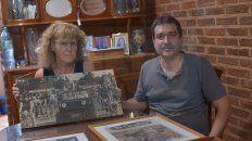 Su hija María Ángela y su nieto Francisco junto a los cuadros que reflejan su rica historia.