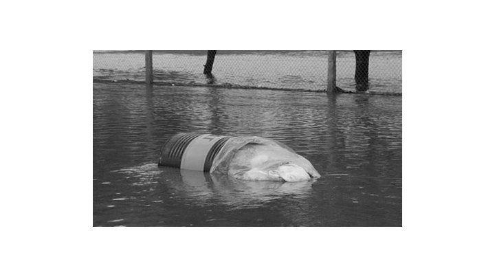 El tacho con residuos peligrosos en el agua. Foto Leonardo Guevara.