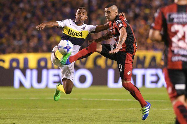 Fernando Telechea intenta obstruir el avance Xeneize encabezado por Wilmar Barrios.