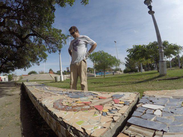 Andrés Leiva mirando su obra en los bancos de cemento que ahora están llenos de imágenes y colores.