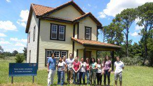 Estudiantes y tutores frente a la vivienda de madera en la Experimental del INTA Concordia.