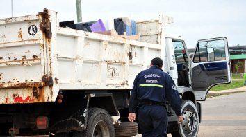 Un bombero salva del agua colchones que son trasladados en un camión de la Municipalidad de Concordia.