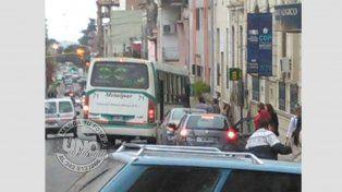 Calle Corrientes. Dos vehículos taponando la parada obligan a los pasajeros a subir en pésimas condiciones, además de dificultar el tránsito.
