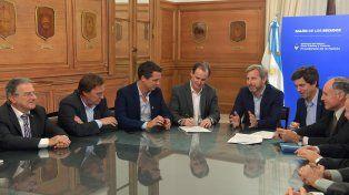 El gobernador firmando el convenio en el Salón de los Escudos.