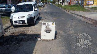 En calle 25 de Mayo señalizaron un gran pozo con un lavarropas