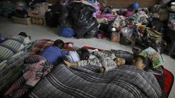 Florencia Cortes, de 37 años, duerme junto a su hijo Jonatan en una escuela. (AP Foto / Natacha Pisarenko)