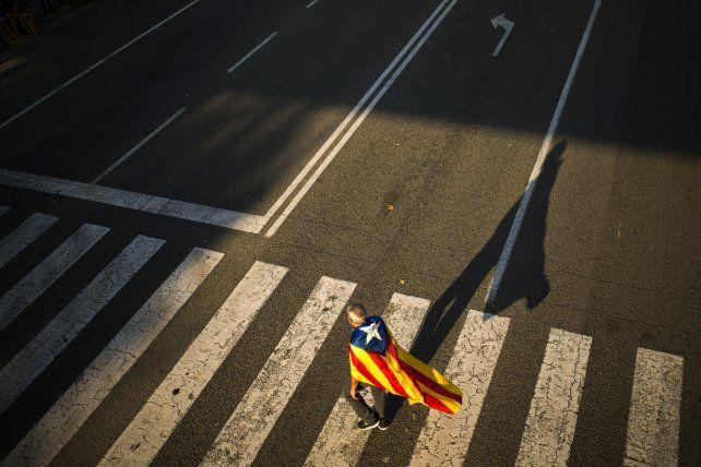 Un hombre con una bandera de la independencia de Cataluña camina hoy por Barcelona. Foto AP / Francisco Seco.