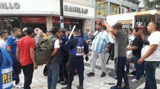 El hombre de camiseta argentina es el que maneja la mercadería en los puestos.