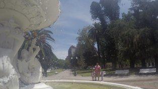 Una papá con sus hijas disfrutando de la fuente funcionando en la plaza Alvear. Foto UNO.