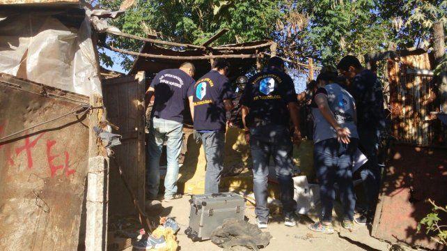 Policias y testigos entre las casas de cartón.