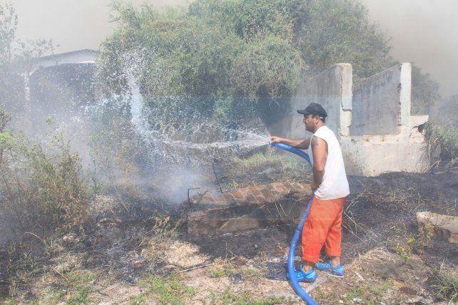 Un municipal tirando agua en los límites. Foto UNO Juan Ignacio Pereira. <div><br></div>