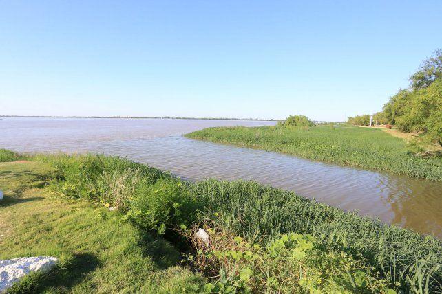 La imagen es tan bella como peligrosa. El contaminado arroyo Las Viejas desemboca en el río Paraná y contamina la playa del Thompson. Foto UNO Archivo. Diego Arias.
