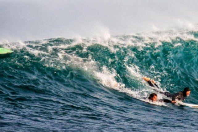 El momento justo en que otro surfista lo ayuda a salir del agua.