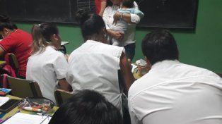 El preciso momento cuando la profesora carga en brazos a la criatura para que la joven madre y alumna pueda seguir con atención la clase que se desarrollaba.
