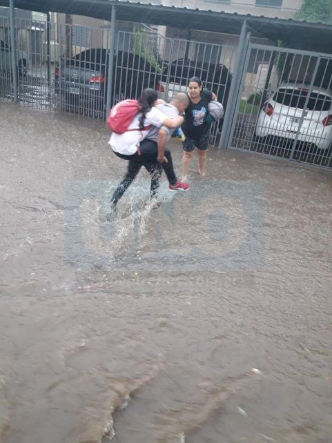 A los saltitos. El colectivero cruzó la calle inundada y dejó a la nena con la madre.