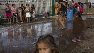 Desborde. Migrantes toman un baño en un refugio temporal.