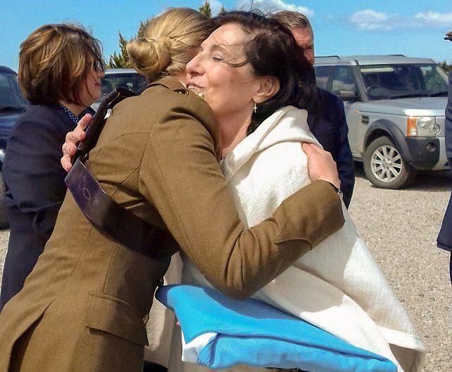 Islas. María Cristina Scavarda es saludada en Malvinas por una oficial británica tras recibir la bandera nacional.