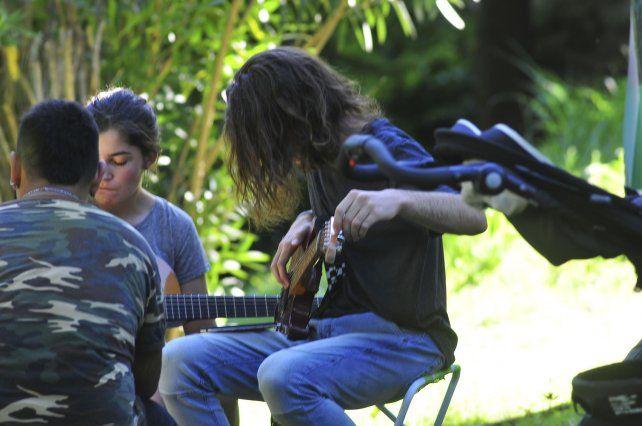 El guitarrista afina en el espacio abierto para los músicos.