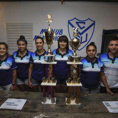 Con el premio. Las jugadoras de la V Azulada junto al entrenador Antonio López, exhibiendo los dos trofeos que sumó este año a las vitrinas del club.